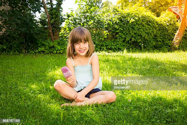 Portrait of happy little girl sitting on a meadow with blueberry ice lolly