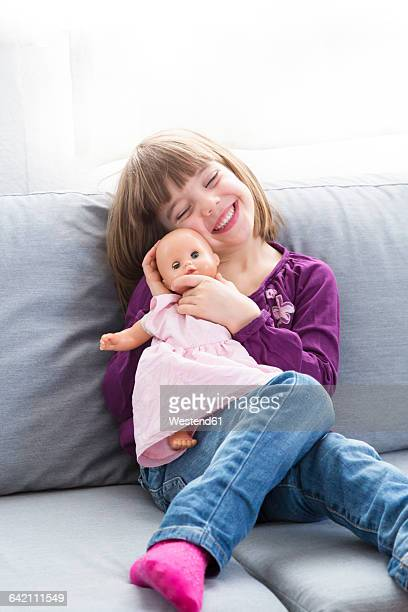 Portrait of happy little girl sitting with her doll on the couch