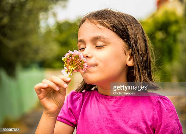 Portrait of happy little girl smelling flower