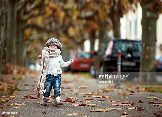 Portrait of happy little girl wearing big scarf and woolly hat in autumn