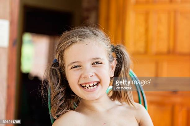 Portrait of happy little girl with braids and tooth gaps