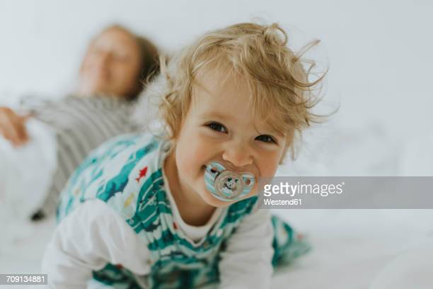 portrait of happy little girl with mother in bed - pacifier stock pictures, royalty-free photos & images