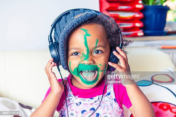 portrait of happy little girl with painted face listening music with headphones - funny black girl stock photos and pictures