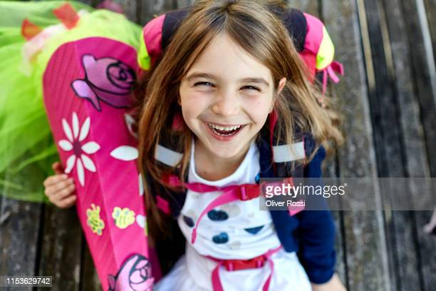 portrait of happy little girl with school cone - first day of school stock pictures, royalty-free photos & images