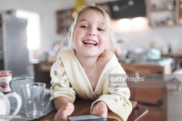 portrait of happy little girl with smartphone in the kitchen - ein mädchen allein stock-fotos und bilder