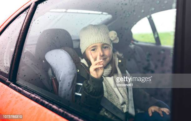 Portrait of happy little girl with wool cap doing victory sign while travelling in car