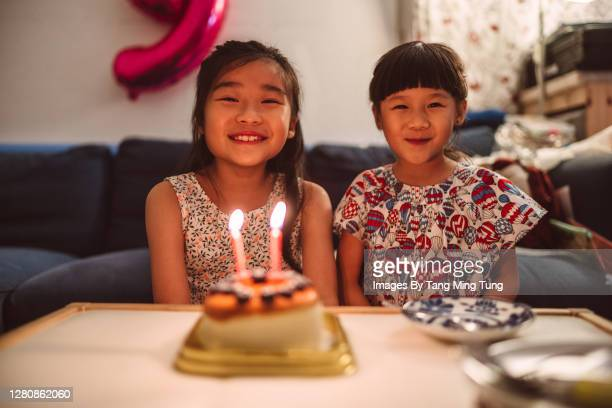 portrait of happy little sisters with birthday cake at home - happy birthday images for sister stock pictures, royalty-free photos & images