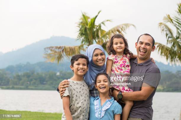 portrait of happy malaysian family in the park - malaysian culture stock pictures, royalty-free photos & images