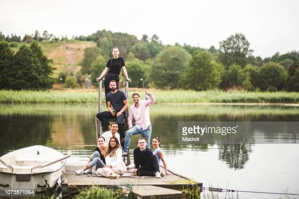 portrait of happy male and female friends on jetty over lake during weekend getaway - vertäut stock-fotos und bilder
