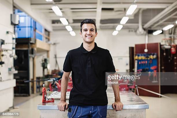 portrait of happy male auto mechanic student standing in workshop - 18 19 jahre stock-fotos und bilder