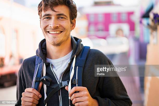 portrait of happy male backpacker in town - rucksacktourist stock-fotos und bilder