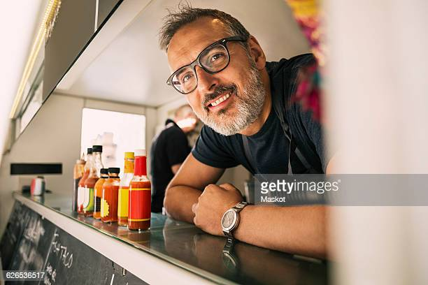 Portrait of happy male chef leaning on counter at food truck