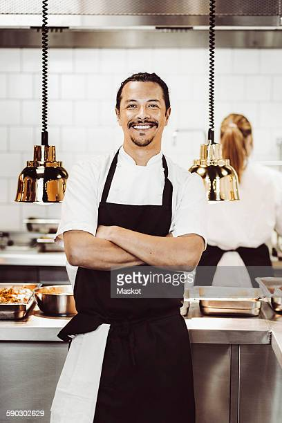 Portrait of happy male chef standing arms crossed in commercial kitchen