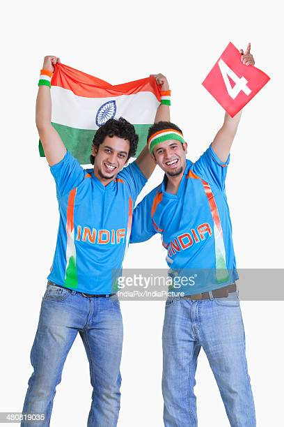 Portrait of happy male cricket fans in jerseys cheering over white background
