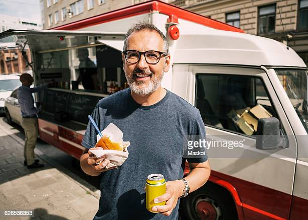 Portrait of happy male customer standing against food truck in city