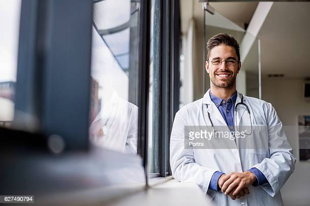 Portrait of happy male doctor standing by window