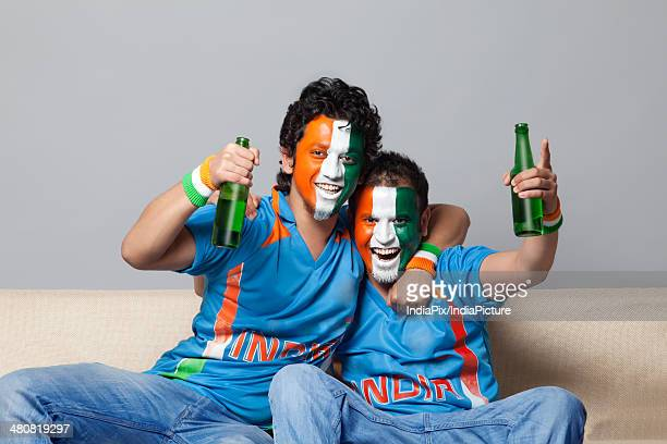 Portrait of happy male friends with face painted in tricolor enjoying beer together at home