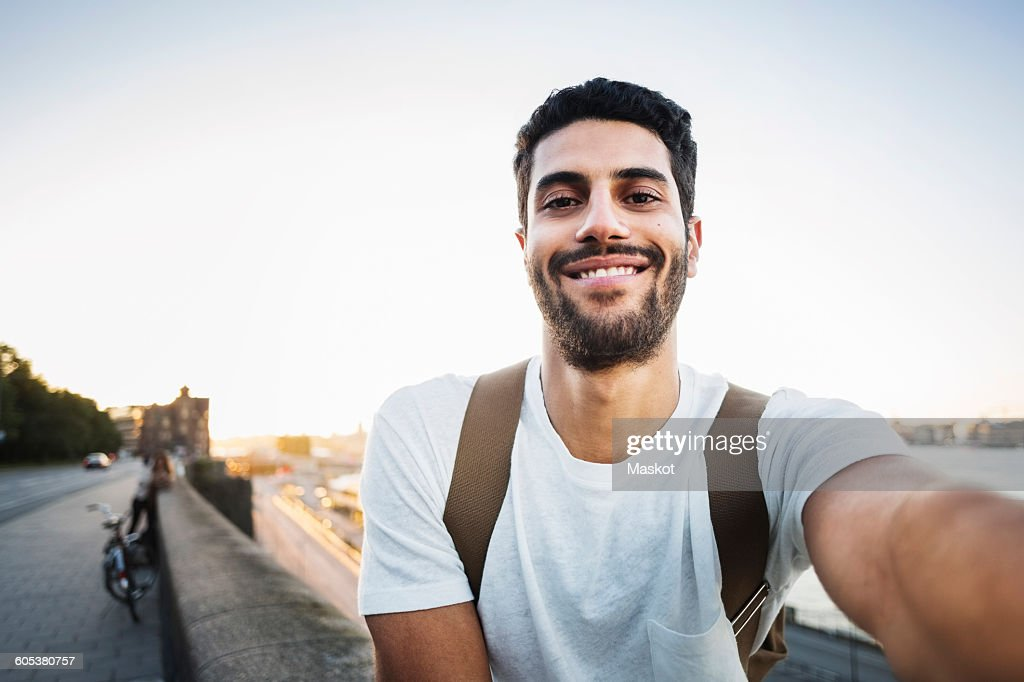 Portrait of happy male tourist sitting on retaining wall of bridge : Stock Photo