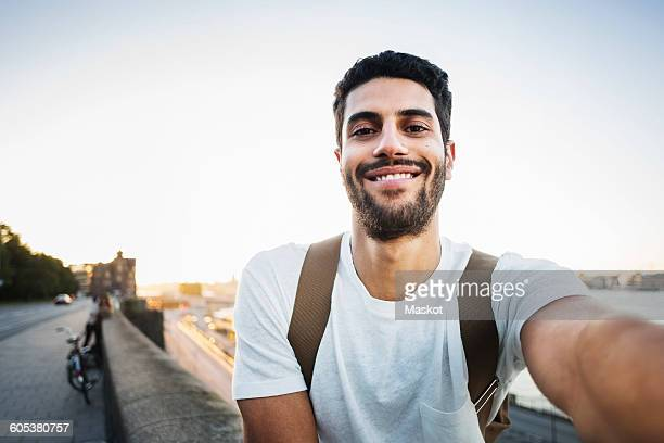 portrait of happy male tourist sitting on retaining wall of bridge - hommes photos et images de collection