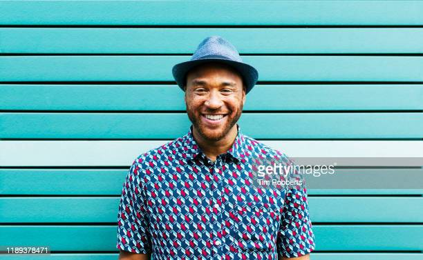 portrait of happy man against blue wall - hipster fotografías e imágenes de stock