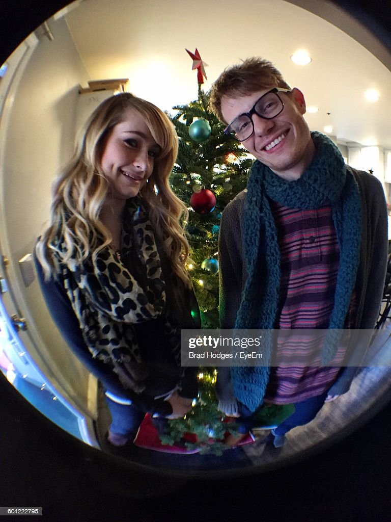Portrait Of Happy Man And Woman Against Christmas Tree Seen Through Peephole : Stock Photo