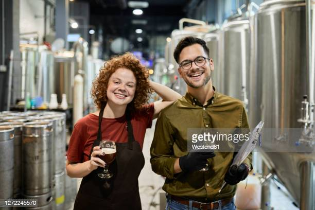 portrait of happy man and woman holding clipboard and beer glass in craft brewery - brewery stock pictures, royalty-free photos & images