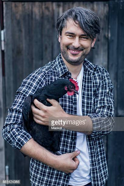 Portrait of happy man carrying hen at poultry farm