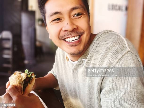 Portrait Of Happy Man Eating Food At Home