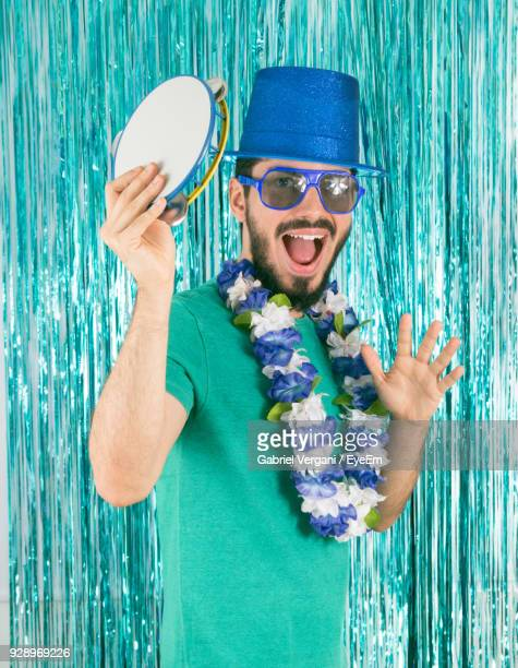 portrait of happy man holding pandeiro against wall - pandeiro stock photos and pictures