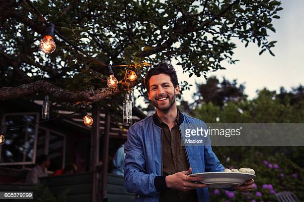 Portrait of happy man holding plate while standing at yard during dinner party