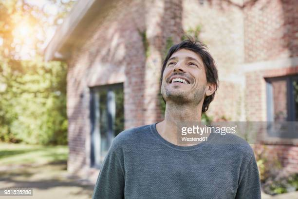 portrait of happy man in front of his home - blick nach oben stock-fotos und bilder
