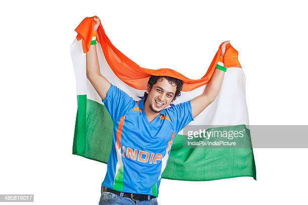 Portrait of happy man in Indian cricket team jersey holding national flag over white background