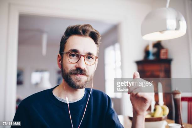 Portrait of happy man listening to music in headphones at home