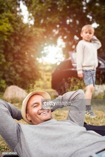 Portrait of happy man relaxing with boy standing at background in park