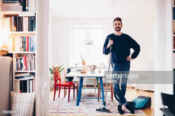 Portrait of happy man standing with vacuum cleaner in dining room at home