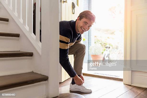 portrait of happy man tying shoelace at doorway - leaving stock pictures, royalty-free photos & images