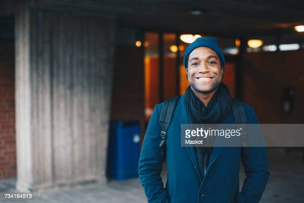 portrait of happy man wearing blue warm clothing and knit hat standing in campus - college student stock pictures, royalty-free photos & images