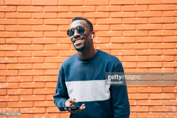 portrait of happy man wearing sunglasses listening music with wireless earphones and smartphone - generation y stock-fotos und bilder