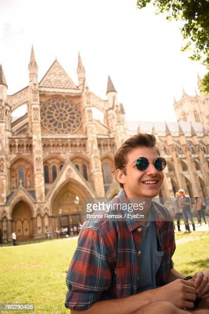 Portrait Of Happy Man Wearing Sunglasses While Sitting Against Westminster Abbey