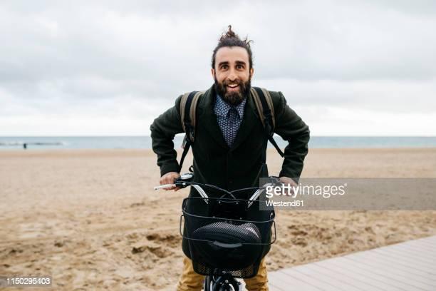 portrait of happy man with e-bike at the beach - velo humour photos et images de collection