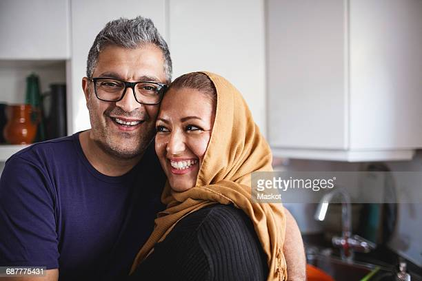portrait of happy man with woman in kitchen at home - muslim couple stock pictures, royalty-free photos & images