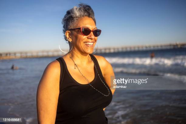 portrait of happy mature black woman at the beach - sunglasses stock pictures, royalty-free photos & images