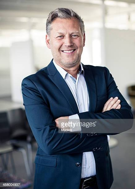 Portrait of happy mature businessman standing arms crossed in office