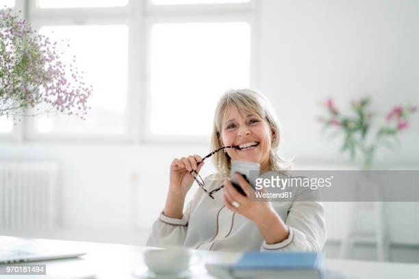 portrait of happy mature businesswoman holding cell phone at desk - weibliche angestellte stock-fotos und bilder