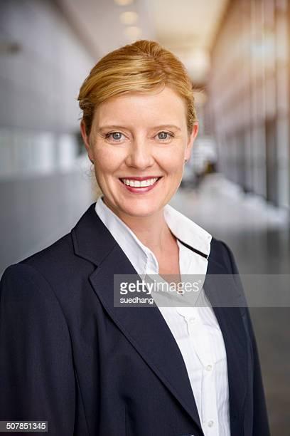 Portrait of happy mature businesswoman in office corridor