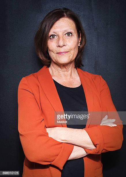 Portrait of happy mature businesswoman standing arms crossed against wall