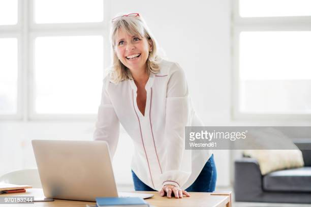 portrait of happy mature businesswoman with laptop leaning on desk - bluse stock-fotos und bilder