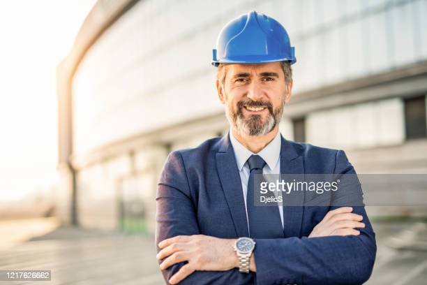 portrait of happy mature engineer wearing hardhat and looking at camera. - real estate developer stock pictures, royalty-free photos & images