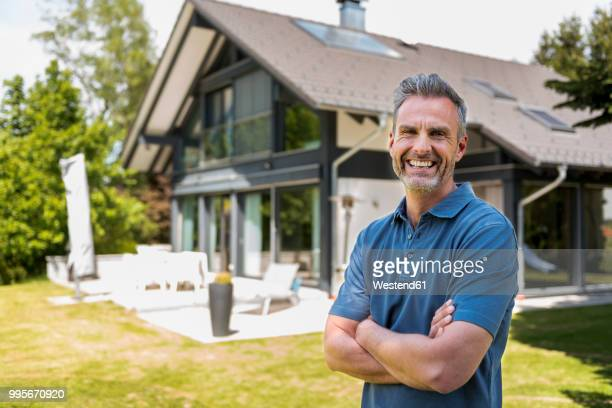 portrait of happy mature man in garden of his home - ein mann allein stock-fotos und bilder