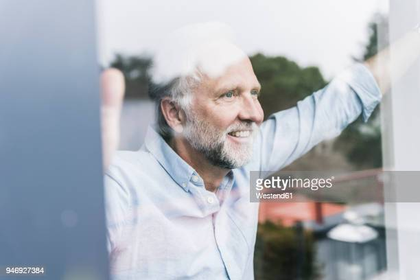Portrait of happy mature man looking out of windowpane